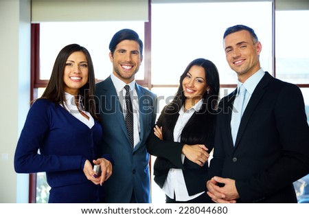 Group of cheerful business people standing in office - stock photo