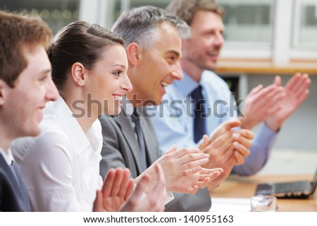 Group of cheerful businesspeople sitting in a row on a presentation and clapping