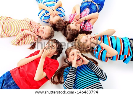 Group of cheerful children lying on a floor together. Isolated over white. - stock photo
