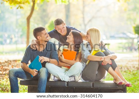 Group of cheerful college students sitting together in a university campus - stock photo