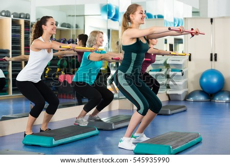 Group of cheerful different age women having aerobic train  in sport club . Selective focus
