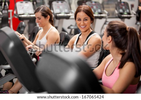 Group of cheerful female friends chatting and enjoying their class in a gym - stock photo