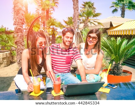 Group of cheerful friends having fun using laptop computer at beach bar - Young people cocktails  party before sunset - Concept of summer tropical holiday traveling around the world  - Sun halo filter - stock photo