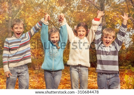 Group of cheerful friends holding hands in the autumnal park - stock photo