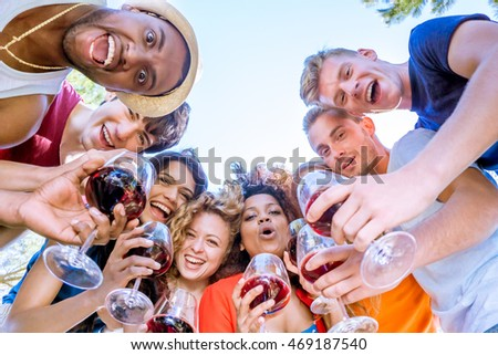 group of cheerful friends in a circle with glasses of red wine looking down at camera