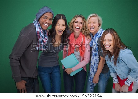 Group of cheerful friends posing together on green background - stock photo