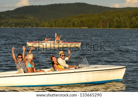 Group of cheerful friends racing with motorboats on river - stock photo