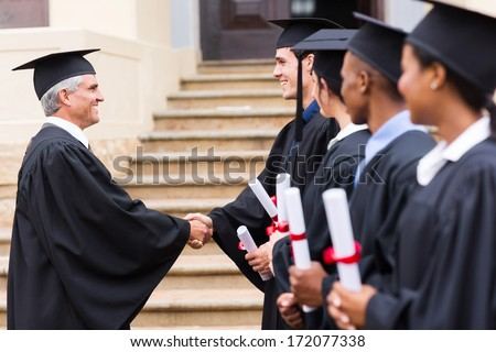 group of cheerful graduates in line handshaking with dean - stock photo