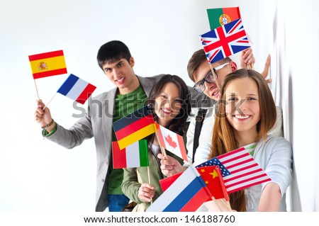Group of cheerful happy students holding international flags and looking at camera leaning on white wall at campus. International education concept - stock photo