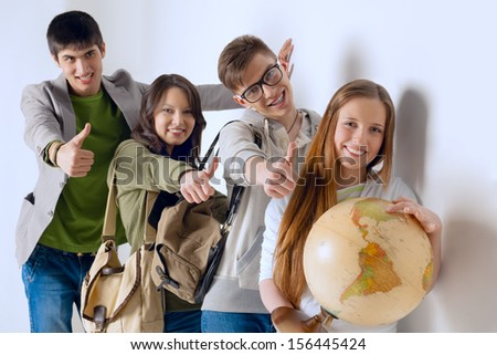 Group of cheerful happy students holding world globe and looking at camera leaning on white wall at campus and showing thumbs up. International education concept - stock photo