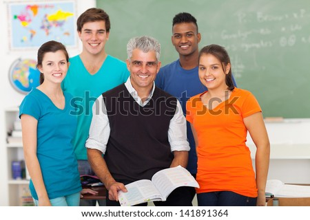 group of cheerful high school students in classroom with senior teacher - stock photo