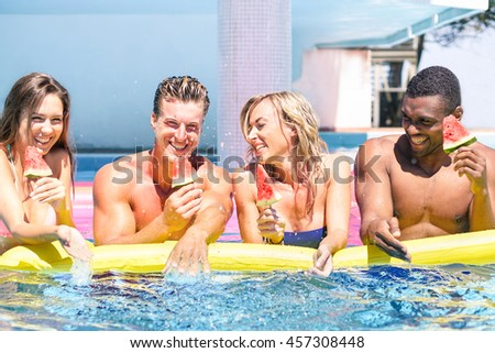 Group of cheerful people eating watermelon during swimming pool party - Multi-ethnic young friends having fun in hotel resort - Vacation and friendship concept - Soft vivid filter with vintage editing - stock photo