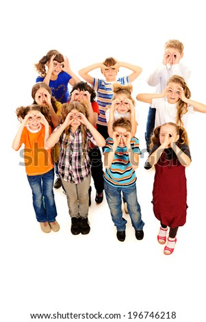 Group of cheerful schoolchildren standing together and facing the same direction. Isolated over white. - stock photo