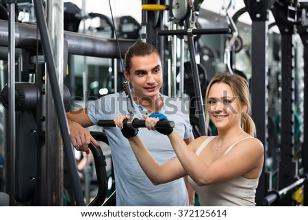 Group of cheerful smiling young adults having power training in fitness club. Focus on guy