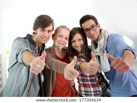 Group of cheerful students showing thumbs up - stock photo