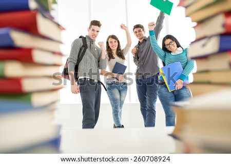 Group of cheerful students standing among the books with arms raised in a fist in school hall and looking at camera. - stock photo