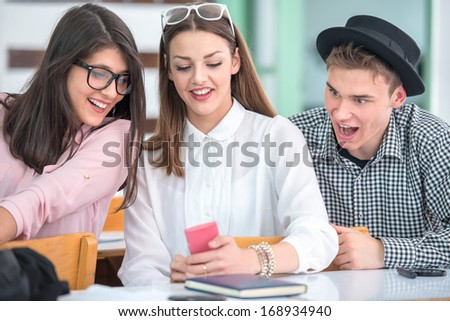 Group of cheerful students using mobile phone together - stock photo