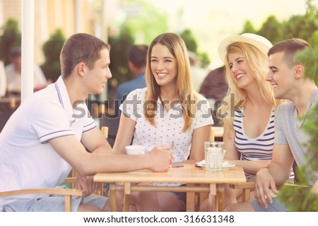 Group of cheerful teenage friends hanging out in a outdoor cafe - stock photo