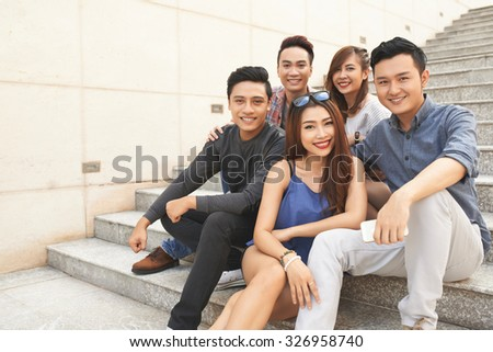 Group of cheerful teenagers posing on stairs