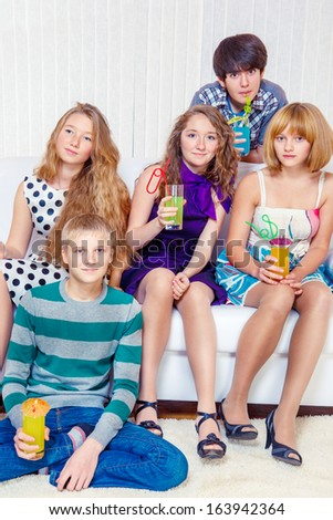 Group of cheerful teenagers with beverages in a living room