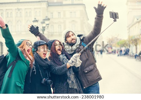 Group Of Cheerful Tourists Taking Selfie Using Smart Phone And Monopod - stock photo