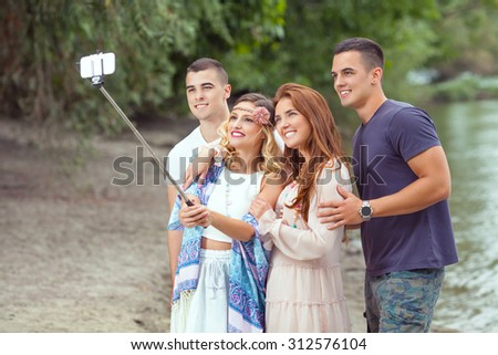 Group of cheerful young friends on the beach taking photos using selfie stick - stock photo