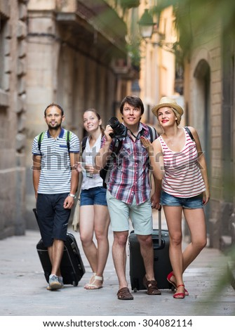 Group of cheerful young friends walking through the city with travel bags. Selective focus  - stock photo