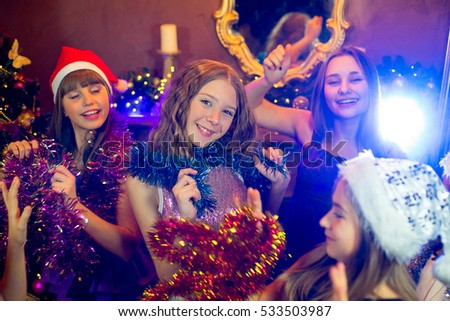 Group of cheerful young girls celebrating Christmas near the Christmas tree with lights. Disco. First plan
