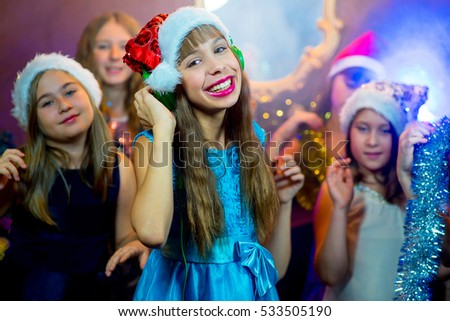 Group of cheerful young girls celebrating Christmas near the Christmas tree with lights. Headphones