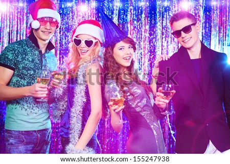 Group of cheerful young people celebrating Christmas at the nightclub. - stock photo
