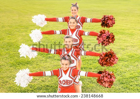 Group of cheerleaders in action with female coach - Concept of unity and team sport - Training at college high school with young happy fit teenagers - stock photo