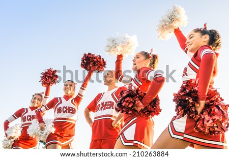 Group of cheerleaders in action with male coach - Concept of unity and team sport - Training at college high school with young female teenagers - stock photo