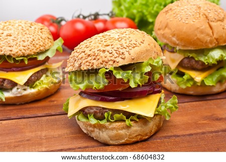 group of cheeseburgers with ingredients on wooden table - stock photo