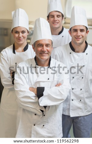 Group of Chef's smiling and standing in kitchen