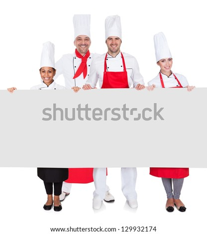 Group of chefs presenting empty banner. Isolated on white - stock photo