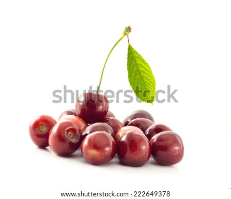 Group of cherries on the white background and with one  cherry with a leaf on the top