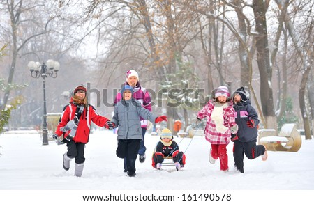group of children and adult playing on snow in winter time, young girl pulling sister through snow on sled - stock photo
