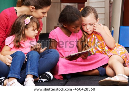 Group of children and educator with picture book in a kindergarten - stock photo