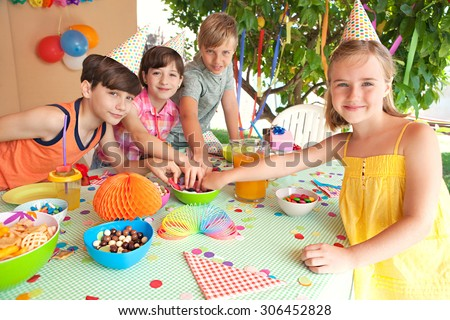 Group of children at a home garden birthday party having fun and eating sweets and party food, outdoors. Kids enjoying a party wearing paper hats and blowing party blowers on sunny day, lifestyle. - stock photo