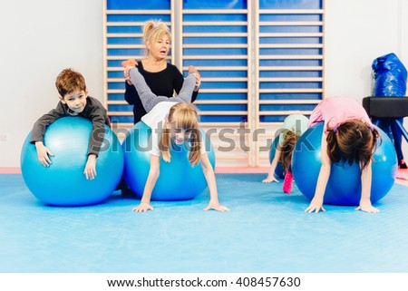 Group of children at physical education, exercising with fitness balls - stock photo