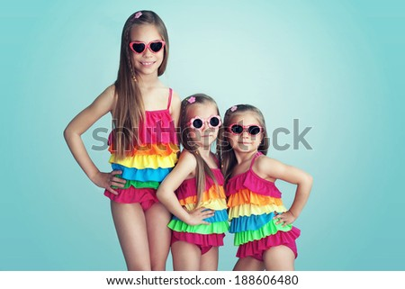 Group of children dressed in fashion swimsuits posing on aqua blue background - stock photo
