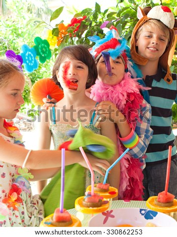 Group of children dressing up in fancy dresses at a colorful birthday party in a home garden with bright decorations, party food and with joyful expressions, outdoors lifestyle. Kids activities fun.