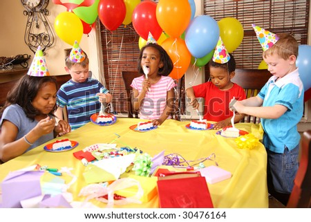 Group of children eating cake at birthday party - stock photo