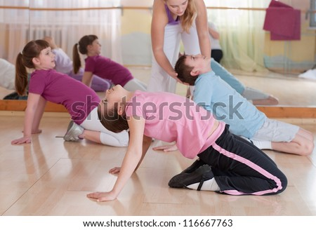 group of children engaged in physical training in the gym. Horizontal.