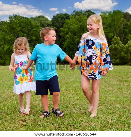 Group of children holding hands while walking at park - stock photo