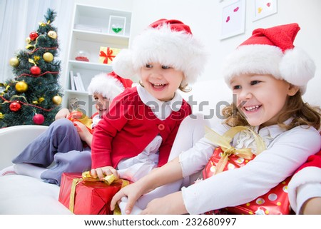 Group of children in Christmas hat with presents playing on couch