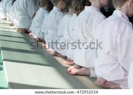 Group of children in kimono sitting on tatami on martial arts training seminar