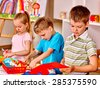 Group of children  in preschool scissors cut paper. - stock photo
