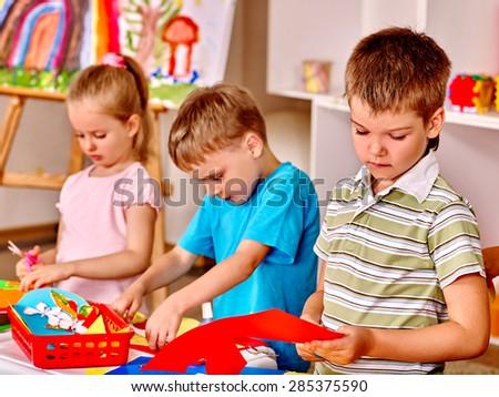 Group of children  in preschool scissors cut paper. - stock photo