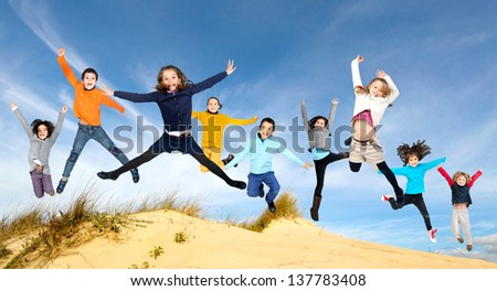 Group of children jumping outdoors - stock photo